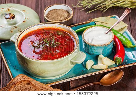 Ukrainian and Russian traditional beetroot soup - borscht in clay pot with sour cream spice garlic pepper dried herbs and bread on dark wooden background healthy food. Ingredients on table.