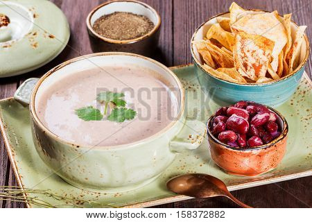 Cream soup with beans vegetables herbs and crackers on plate on dark wooden background. Homemade food. Ingredients on table