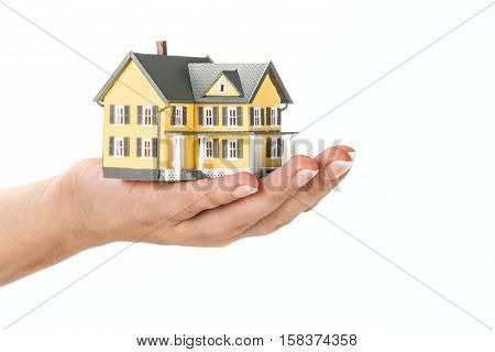 Women's Hand Holding a Model of a House