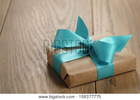 rustic craft paper gift box with blue ribbon bow on wood table, shallow focus