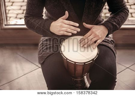Girl drummers hands playing percussion bongo in a house