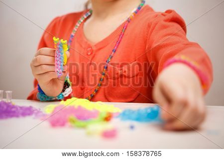 girl weaving of colored rubber band bracelet, close up