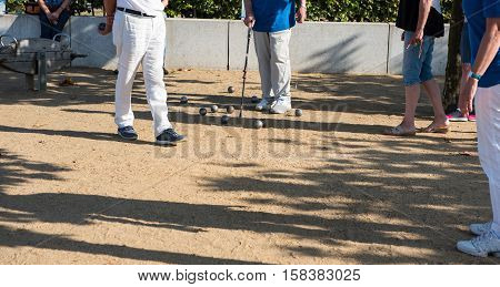 Player playing boules during a tournament on sand poster