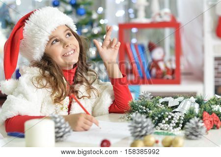 Portrait of cute little girl in Santa hat writing letter and holding crossed fingers