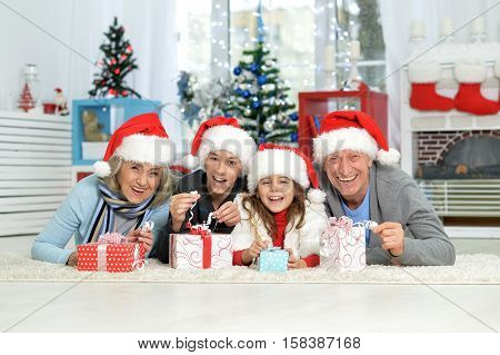 Happy grandparents with grandchildren celebrating Christmas lying on the floor with gifts