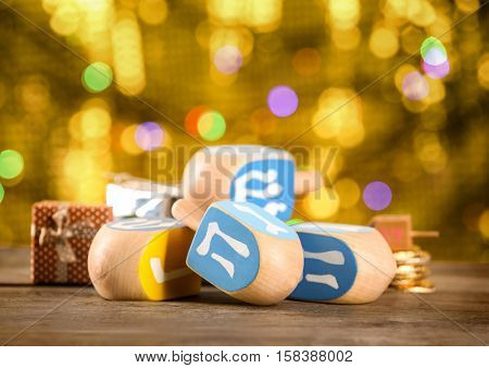 Dreidels for Hanukkah on wooden table against defocused lights
