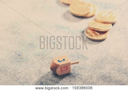 Wooden dreidel for Hanukkah on light sparkling background
