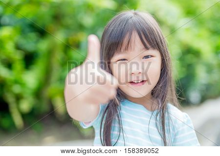 little girl smile happily and thumb up in the parkasian