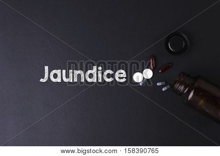 Jaundice word with medicine and bottle - Health concept. Medical conceptual