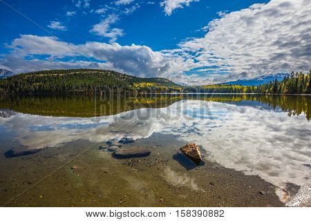 Pyramid Mountain and white clouds reflected in the smooth water of Pyramid Lake. Sunny morning in the Rocky Mountains, Canada
