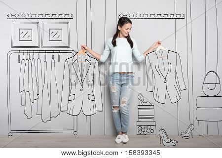 Difficult choice. Happy delighted young woman holding clothes on hangers while choosing between them and smiling.