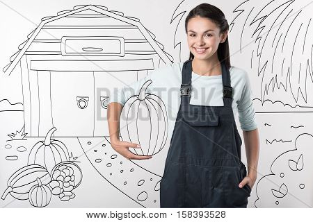 Nature products. Young pretty delighted farmer woman standing in the yard and smiling while holding a pumpkin.