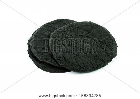 Organic active carbon charcoal cookies on white background.