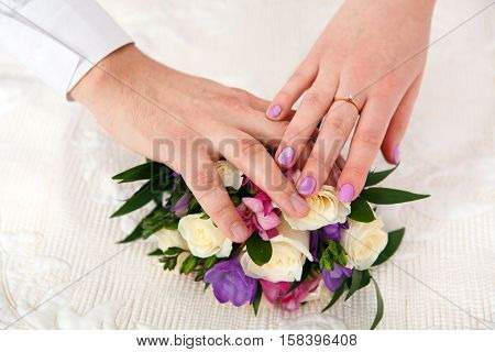 Hands of the newlyweds and the bride's bouquet. The bride and groom love each other. The tender feelings of two people in the Wedding day.
