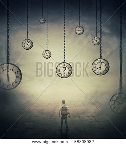 Surrealistic image with a man lost in time standing in a foggy street in front of huge clocks set to different times. Hour perception and time travel concept.