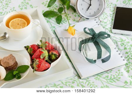 Breakfast in bed of green tea strawberries sweets on a white tray next to gift box yellow rose self phone alarm clock. Happy woman morning breakfast in bed and gift concept. Horizontal. Daylight.