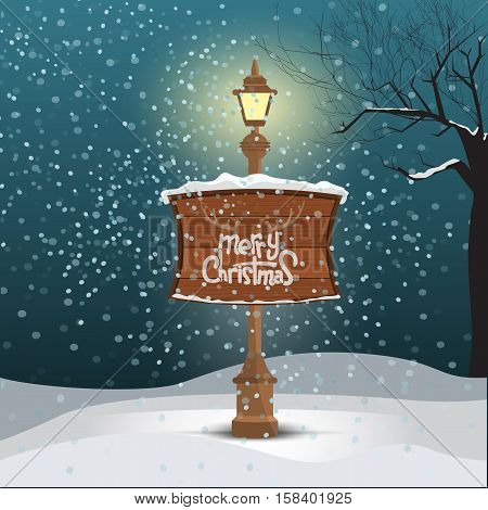 Christmas greeting card - snowy winter background. Street lamp and wood board with merry christmas calligraphy text writing.