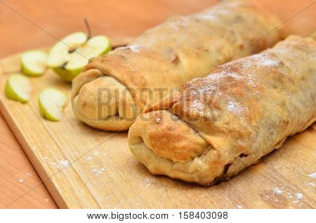 homemade cakes - roll strudel. Against the background paper for baking. Space for text. Festive cakes. In the background is scattered flour half an apple.