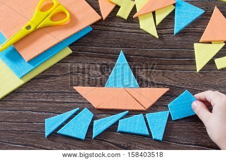 Hand Assembled Child Figure Ship Tangram Puzzle Square Wooden Table Above. The Concept Of Early Chil