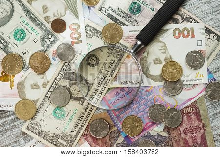 Different collector's coins and banknotes with a magnifying glass wooden background
