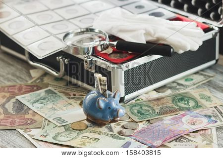 Different collector's coins and banknotes with a magnifying glass and piggy bank wooden background