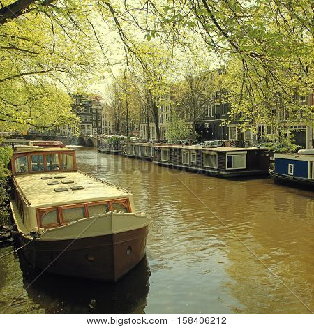Beautiful Amsterdam scene with traditional dutch old buildings and houseboats in the canal Jordan neighborhood, Amsterdam, the Netherlands. Square vintage toned image