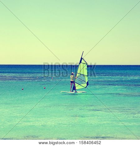 Back view of young woman windsurfer in Crete island Greece. Square toned image