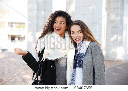 Two beautiful young women hugging on street background. Caucasian lady wearing scarf. African young curly woman wearing white big scarf and holding bag. Look aside.