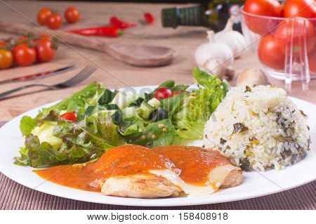 Parmegiana Chicken Fillet rice and Fresh and healthy Salad over a wooden table