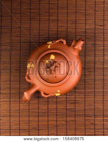 brown Chinese teapot of Yixing clay with traditional ornament on bamboo Mat