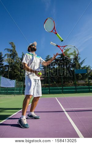 Professional tennis player juggling with rackets. He is having a good time before starting the game.
