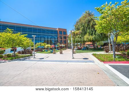 Mountain View, CA, United States - August 15, 2016: Google Building 1950 near the main Googleplex, with its relaxing green area and employees on their lunch break.Google is a multinational corporation