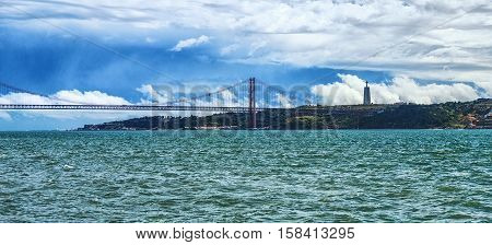 Hanging 25th of April Bridge connecting Lisbon to the north and Almada on the south side of the river Tagus. View on Jesus Christ statue on a hill .