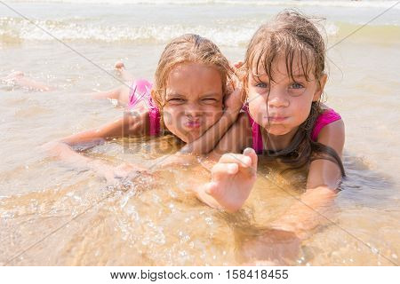 Two Girls Lying In The Shallow Water And Fun Pretending Faces Looking In The Frame