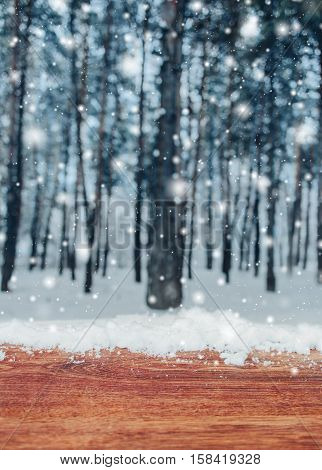 Wooden table with snow place and Christmas background with fir trees and blurred background of winter. Frosty winter landscape in snowy forest