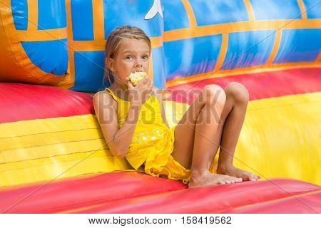 Girl Sits At The Entrance To An Inflatable Trampoline And Eating An Apple