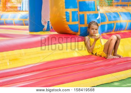 Girl Sits At The Entrance To An Inflatable Trampoline And Eats An Apple