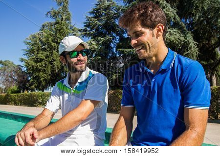 Two professional players hydrating after a hard game of tennis. They are friends and are sitting resting for the game. They are happy and laughing.