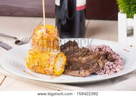 sirloin steak in brown rice and corncob with butter and bonito flakes