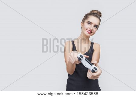 Portrait of a girl with a bun who is wearing a black tank top and holding a video game controller and smiling. Concept of gaming. Mock up