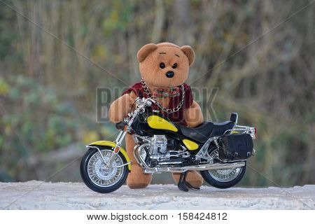 Teddy Bär stands behind a motorcycle outside