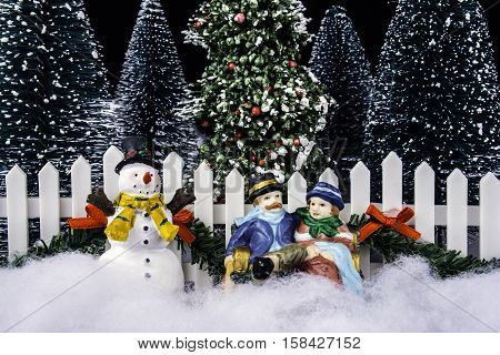 miniature Christmas scene of couple sitting on park bench with snowman pine trees and white picket fence