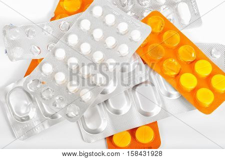 Stack of various pills on withe background