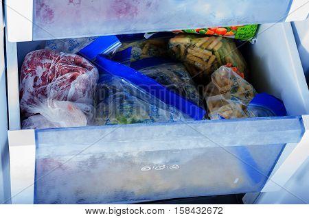 Various frozen vegetables in plastic bags in freezer
