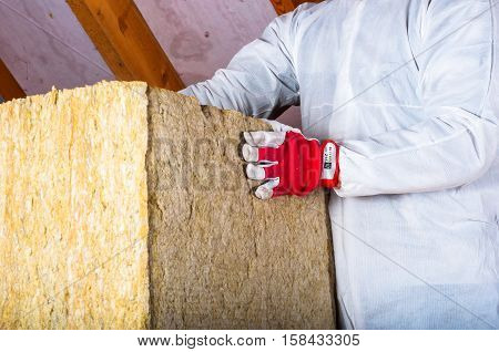 Man installs insulation with rock wool in attic/loft