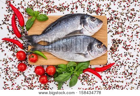Raw Dorado Fish On Wooden Cutting Board With Peppercorns On White Table. Top View, Copy Space