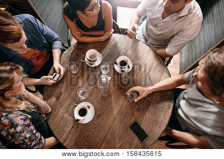 Top view of young people sitting at cafe with cup of coffee on table. Group of friends at coffee shop.