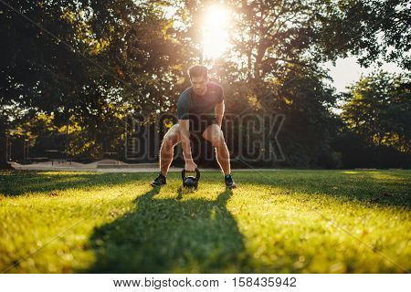 Shot of fit young man exercising with kettlebell outdoors in the park. Strong young guy training at park in morning.