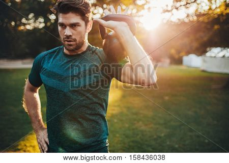 Shot of fit young man exercising with kettlebell in the park. Strong young guy training at park in morning.