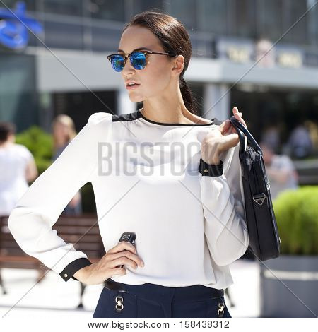 Young beautiful business woman with blue mirrored sunglasses
